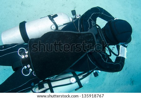 side mount scuba diver swims in the ocean - stock photo