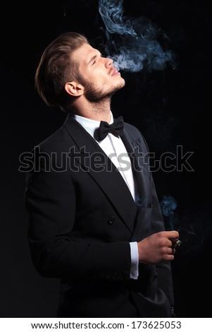 side of an elegant man enjoying his cigar on dark studio background - stock photo