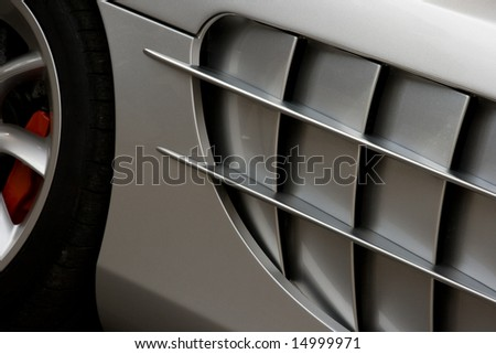 Side of silver super car with large cooling vent - stock photo