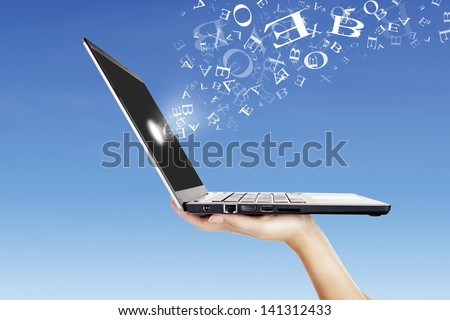 Side of ultrabook laptop computer on the hand with flying alphabet under blue sky - stock photo