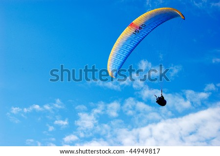 Side paraglider on blue sky with feather clouds - stock photo