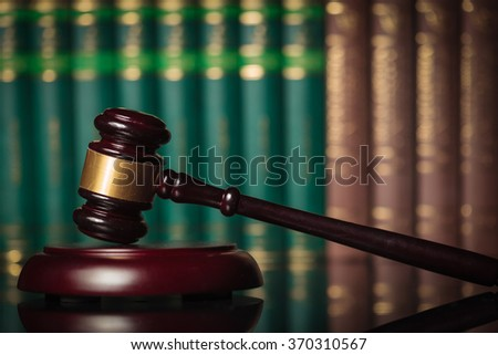 side picture of a judge's gavel in front of a row of law books, learing law concept - stock photo