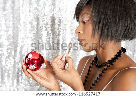 Side portrait close up of an attractive black woman using a Christmas bar ball reflection to apply her lipstick while standing in front of a silver sequins background. - stock photo