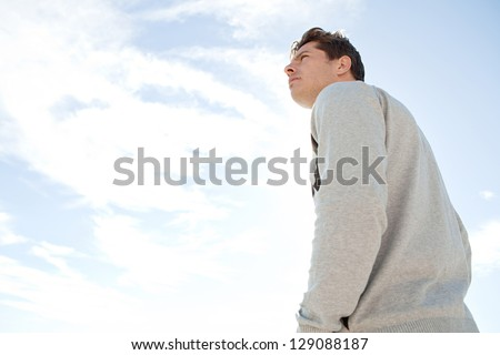 Side portrait low angle view of a man standing and looking ahead against a blue sky being thoughtful. - stock photo