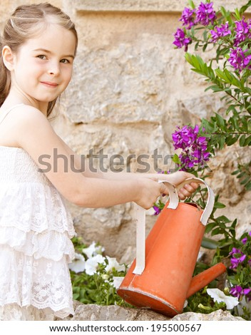 Side portrait of a beautiful young child girl holding a watering can and watering the plants in her holiday home garden, smiling outdoors. Kid helping with home duties while on vacation, lifestyle. - stock photo