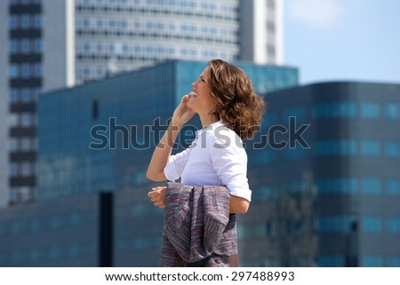 Side portrait of a business woman walking and talking on cell phone in the city - stock photo