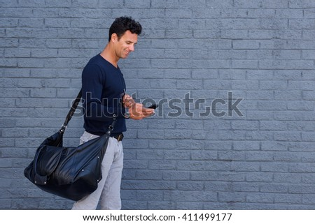 Side portrait of a handsome man traveling with bag and cell phone - stock photo