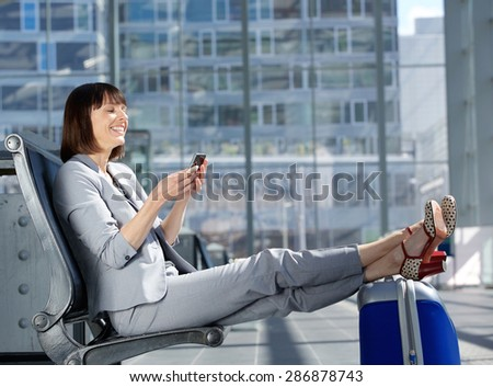 Side portrait of a happy business woman sitting with feet on bag and looking at mobile phone - stock photo