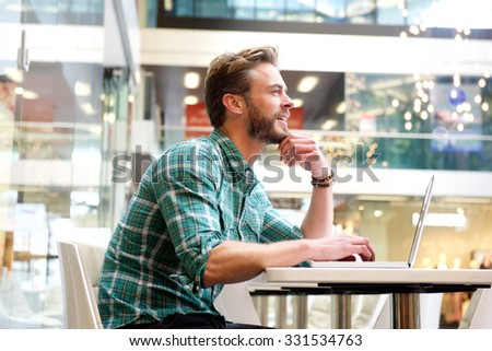 Side portrait of a man sitting in shopping mall with laptop - stock photo
