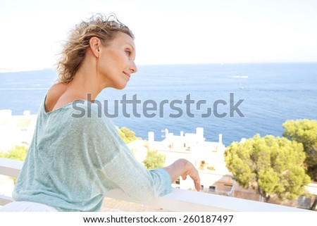 Side portrait of a mature middle age attractive woman relaxing in her holiday resort hotel balcony, contemplating the sea and blue sky during a summer vacation day, outdoors. Beauty and lifestyle. - stock photo