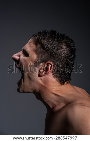 Side portrait of a screaming man - stock photo