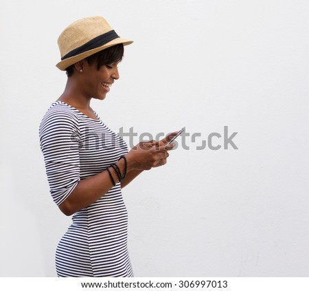 Side portrait of a smiling african american woman walking and reading text message - stock photo