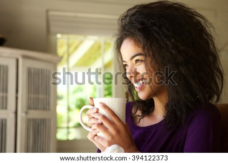 Side portrait of a smiling young woman sitting at home enjoying cup of coffee - stock photo