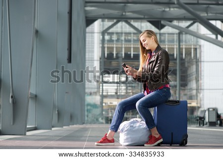 Side portrait of a smiling young woman sitting on suitcase and looking at mobile phone - stock photo
