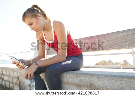 Side portrait of a sporty adolescent girl resting from exercising, using a smart phone to listen to music with headphones, sunny outdoors. Fitness and sport lifestyle, clear sky, exterior. - stock photo