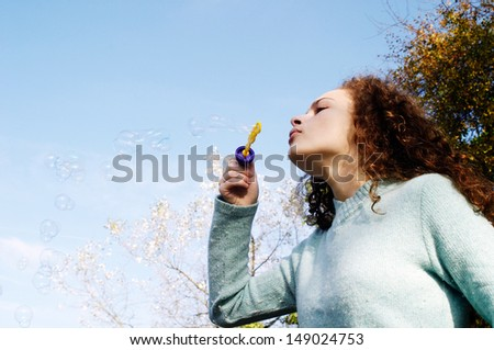 Side portrait of a young girl in a park during the autumn season, wearing a blue jumper and playing at blowing soap bubbles against a blue sky during a sunny winter day. - stock photo
