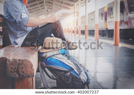 Side portrait of a  young man traveler sitting with map choose where to travel and bag waiting for train at train station, vintage tone filter effected - stock photo