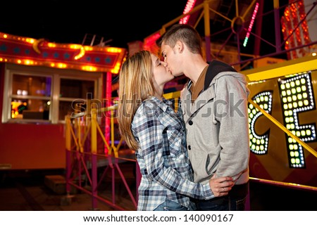 Side portrait of a young teenage couple visiting an attractions park arcade being romantic and kissing with funfair rides and lights in the background during night time. - stock photo