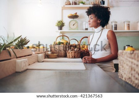 Side portrait of beautiful young woman behind juice bar counter. African female fruit juice bar owner. - stock photo