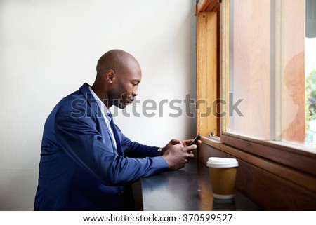 Side portrait of black businessman sitting in a cafe sending text message on cell phone   - stock photo