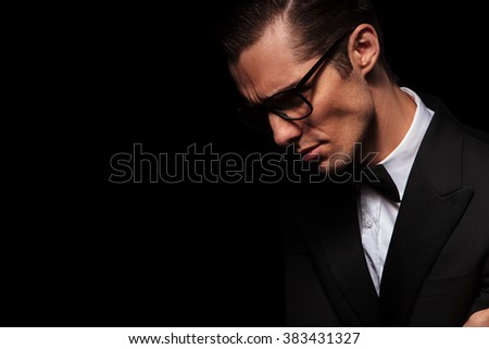 side portrait of classy elegant man in black suit posing in dark studio background looking down  - stock photo