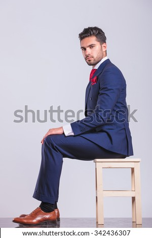 side portrait of man in business suit sitting in studio looking at the camera - stock photo