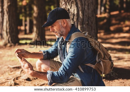 Side portrait of senior man with backpack sitting in a forest and looking at his digital tablet for directions. Mature male hiker using tablet for navigation. - stock photo