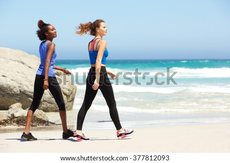 Side portrait of two young sporty women walking on the beach - stock photo