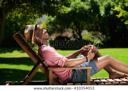 Side portrait of young african guy sitting on chair and listening to music outdoors - stock photo
