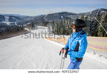 Side portrait of young cute woman skier looking at beautiful mountain landscape at the ski resort on a sunny day. Girl is wearing blue jacket helmet and goggles. Wide angle. Carpathian Mountains - stock photo