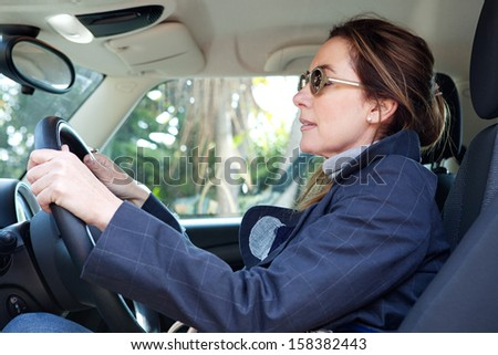 Side portrait view of a mature middle aged smart woman sitting on the drivers seat of a new car, driving through a countryside road during a sunny winter day. - stock photo