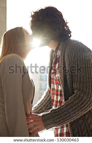 Side portrait view of a young romantic couple kissing while on vacation with the sun rays filtering through their lips. - stock photo