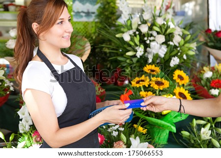 Side portrait view of an attractive shop attentant and business owner woman taking a customer credit card payment at a small florist business store outdoors. Outdoors shopping lifestyle. - stock photo