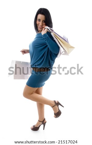 side pose of smiling model holding carry bags with white background - stock photo