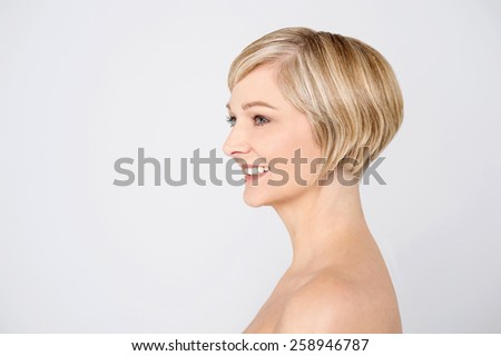 Side pose of smiling topless middle aged woman - stock photo