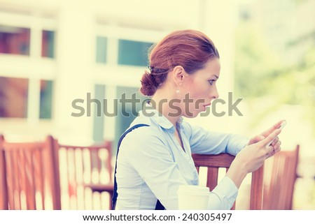 Side profile closeup portrait anxious young girl looking at phone seeing bad news or photos with disgusting emotion on her face isolated outside city background. Human emotion, reaction, expression - stock photo