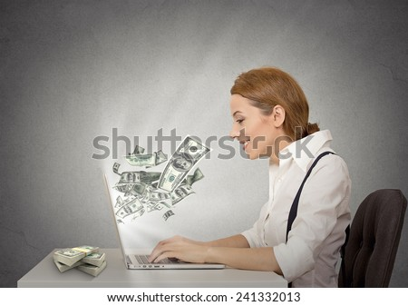 Side profile happy smiling business woman working online on computer earning money dollar bills banknotes flying out of laptop screen isolated grey wall office background. Human face expression  - stock photo