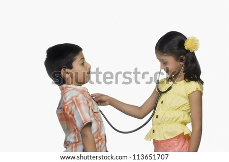Side profile of a girl examining a boy with a stethoscope - stock photo