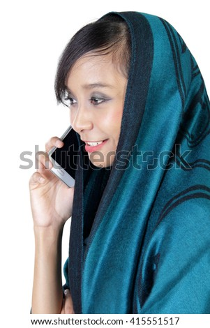 Side profile of an urban muslim woman making a phone call, isolated over white studio background - stock photo