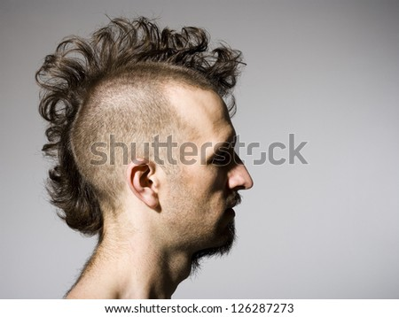 Side profile of man with half shaved hair and beard - stock photo