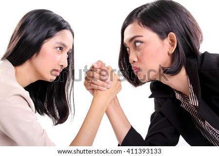 Side profile of two Asian business women doing arm wrestling and staring at each other's eyes, closeup portrait isolated on white background - stock photo