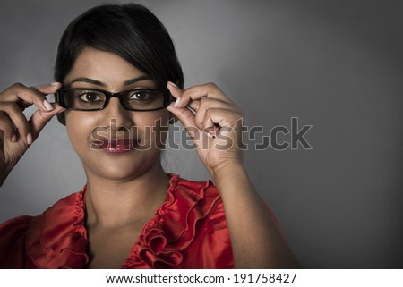 Side profile of woman holding her framed glasses - stock photo