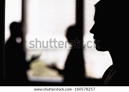 Side profile on businesswoman with coworkers in background - stock photo
