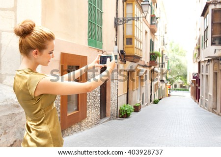 Side profile portrait of a young tourist woman holding up using a smart phone to take photos of destination city street on holiday, outdoors technology. Girl smiling using technology, city exterior. - stock photo