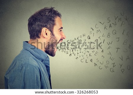 Side profile portrait of young angry man screaming with alphabet letters flying out of wide open mouth isolated on gray wall background  - stock photo