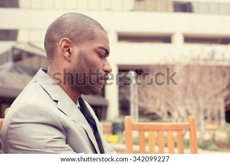 side profile portrait stressed young businessman sitting outside corporate office  looking down. Negative human emotion facial expression feelings. - stock photo