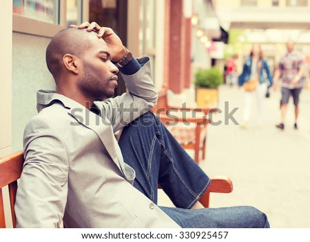 side profile stressed young casual businessman sitting outside corporate office holding head with hands looking down. Negative human emotion facial expression feelings. - stock photo