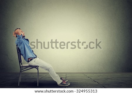 Side profile young business man relaxes in his empty office  - stock photo