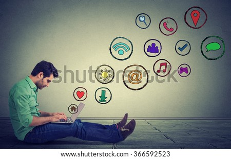 Side profile young man working on laptop using social media application sitting on a floor. Building relationship modern communication technology concept - stock photo