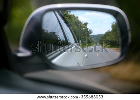 Side rear mirror of car show straight road - stock photo